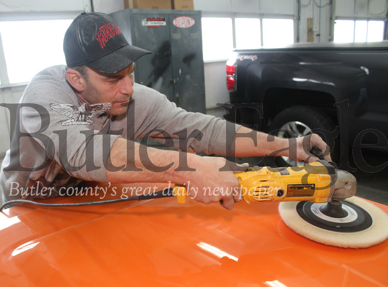 Harold Aughton/Butler Eagle: Painter Tim Maglico at Baglier Collision Center, puts the final touches on the hood of a Chevy pickup truck.