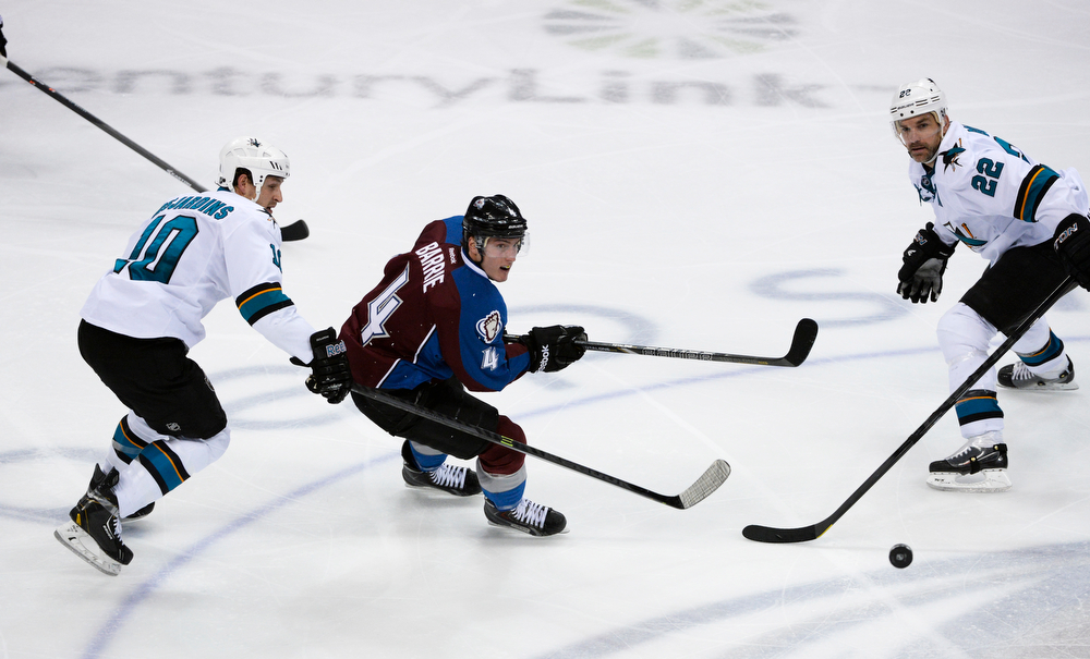 . Colorado Avalanche defenseman, Tyson Barrie, center, goes after a lose puck against Andrew Desjardins, left, and Dan Boyle, San Jose Sharks in the second period of play at the Pepsi Center Saturday afternoon, March 29, 2014. (Photo By Andy Cross / The Denver Post)