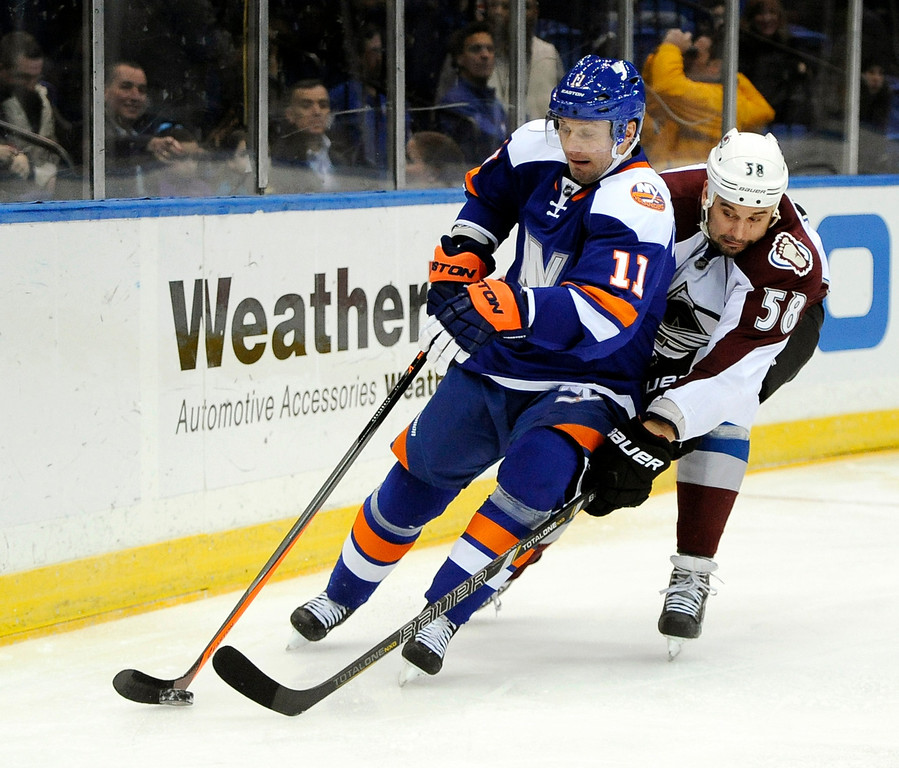 . New York Islanders\' Lubomir Visnovsky (11) and Colorado Avalanche\'s Patrick Bordeleau (58) battle for the puck around the boards in the first period of an NHL hockey game on Saturday, Feb. 8, 2014, in Uniondale, N.Y. (AP Photo/Kathy Kmonicek)