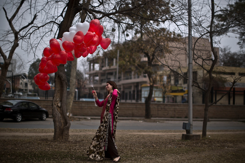 . A Pakistani woman holding red and white heart-shaped balloons pose for a picture taken by another girl on Valentine\'s Day, in Islamabad, Pakistan, Friday, Feb. 14, 2014. (AP Photo/Muhammed Muheisen)