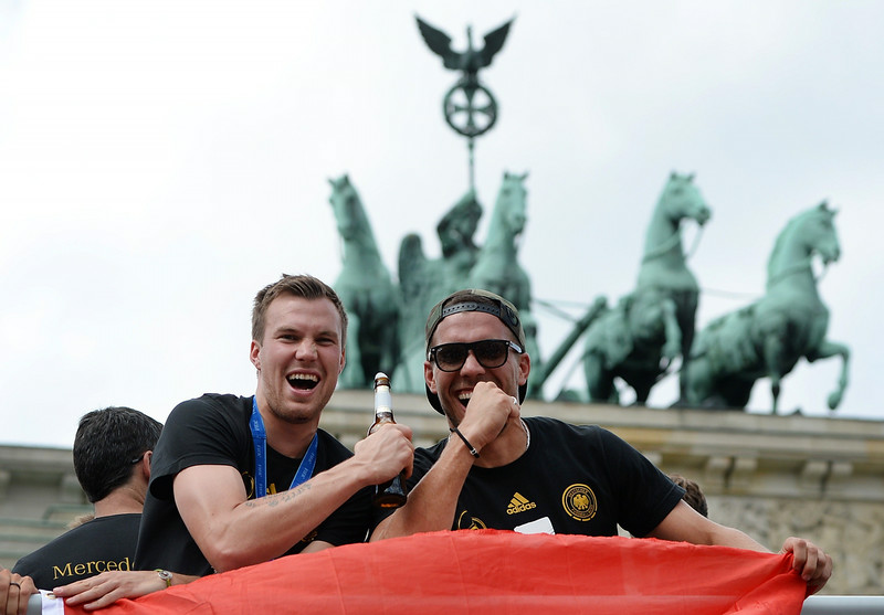. German national football team players Kevin Grosskreutz and Lukas Podolski cheer as they ride in an open-deck bus to Berlin\'s landmark Brandenburg Gate to celebrate their FIFA World Cup title. Germany won their fourth World Cup title, after 1-0 win over Argentina on July 13, 2014 in Rio de Janeiro in the FIFA World Cup Brazil final game.   (DANIEL NAUPOLD/AFP/Getty Images)