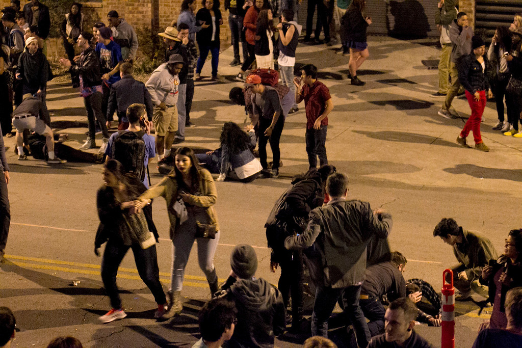 . The crowd scatters seconds after several pedestrians were struck by a vehicle on Red River Street in downtown Austin, Texas, during SXSW on Wednesday March 12, 2014.  (AP Photo/Austin American-Statesman, Jay Janner)