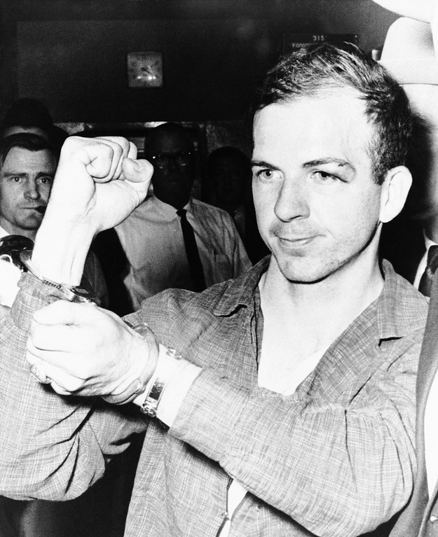 . Oswald, 24, holds up his manacled hands as he is led through the police station. He had been charged with murder in the killing of a Dallas policeman who sought to arrest him in a theater several miles from the assassination scene. Associated Press file