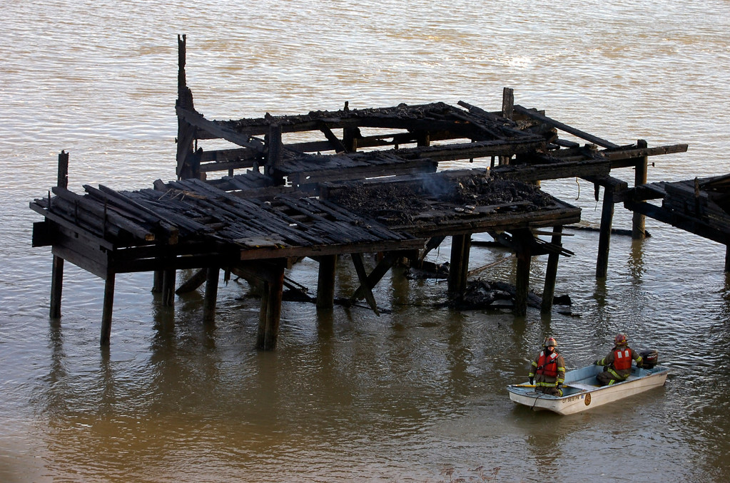 . Firefighters from the C&H sugar plant inspect the remains of a pier as they and firefighters from the Crockett Carquinez Fire Protection District finish up at the site of a pier fire in Crockett, Calif. on Tuesday, Jan. 15, 2013. The cause of the fire on the privately owned pier, which broke out in the early morning hours, is being described as suspicious. (Kristopher Skinner/Staff)