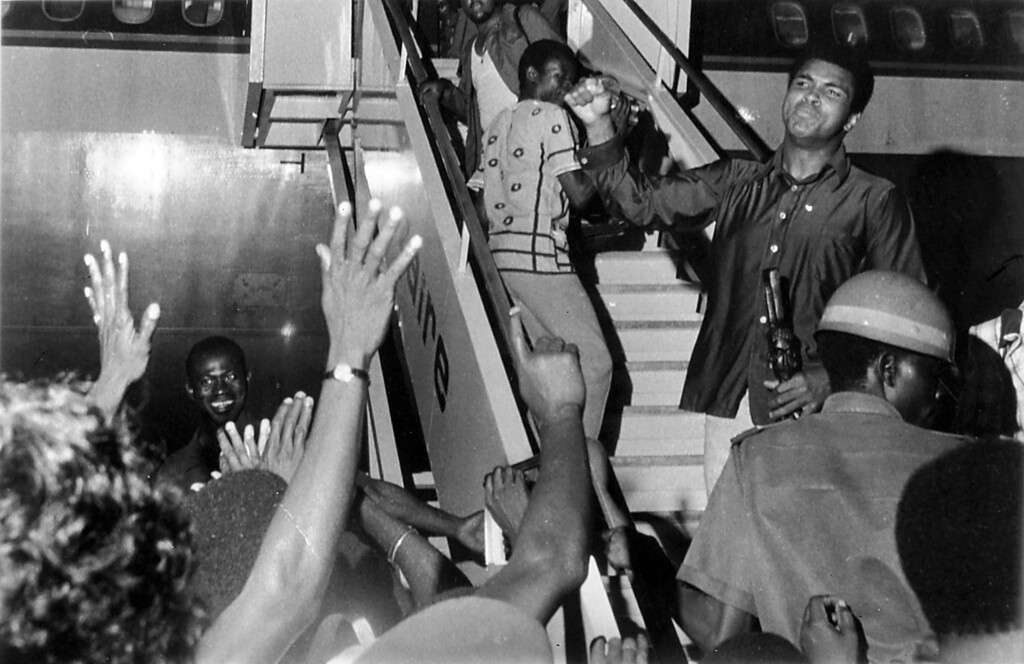 . Muhammad Ali waves to a chanting crowd at Kinshasa\'s N\'Djili airport in Zaire, Nov. 1, 1974, as he boards a plane to return to the United States. (AP Photo)