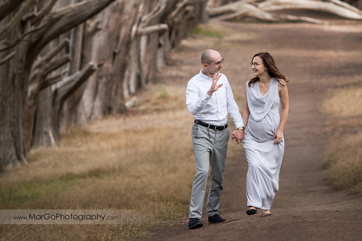 man and pregnant woman in long gray dress walking in the Seal Cove Cypress Tree Tunnel during maternity session