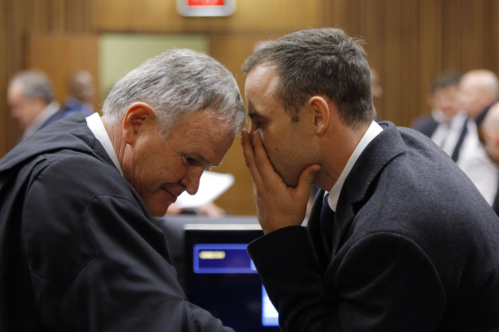 ". Defense team leader Barry Roux (L) talks to South African Paralympic athlete Oscar Pistorius on the second day of his trial at the North Gauteng High Court in Pretoria on March 4, 2014. Almost 100,000 people had signed a petition on Tuesday against an ""offensive\"" advert by Irish bookmaker Paddy Power offering to refund bets made on a guilty verdict in the Oscar Pistorius trial if he walks free.  The ad shows an Oscar statuette with the face of the South African Paralympic athlete and the words: \""It\'s Oscar Time. Money Back If He Walks. We will refund all losing bets on the Oscar Pistorius trial if he is found not guilty.\"" (KIM LUDBROOK/AFP/Getty Images)"