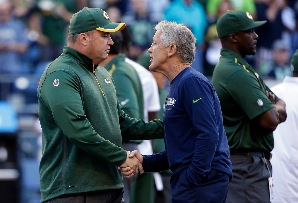 . Green Bay Packers coach Mike McCarthy, left, shakes hands with Seattle Seahawks coach Pete Carroll before an NFL football game, Thursday, Sept. 4, 2014, in Seattle. (AP Photo/Elaine Thompson)