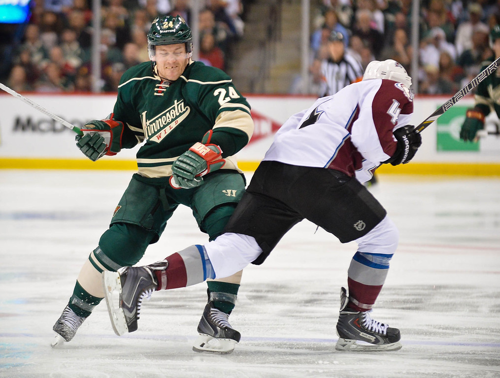 . Minnesota\'s Matt Cooke, left, knees Colorado defenseman Tyson Barrie in the second period.  Cooke was given two minutes for kneeing on the play, which knocked Barrie out of the game. (Pioneer Press: Ben Garvin)