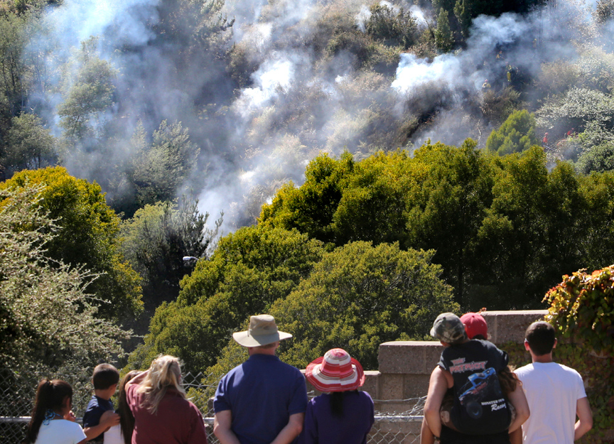. Onlookers watch as smoke bellows from the wooded area by the Fishhook where a wild fire ignited at about 3pm on Thursday, June 20 at southbound Highway 17 in Santa Cruz. (Kevin Johnson/Sentinel)