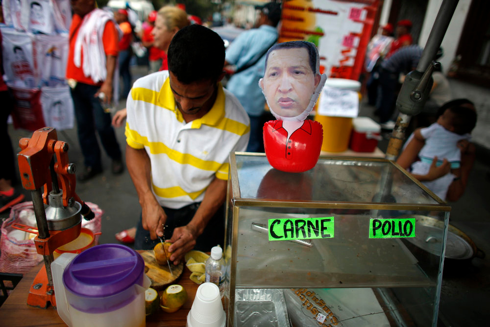 Description of . A man prepares orange juice next to a puppet depicting Venezuela's President Hugo Chavez outside the military hospital after his surprise return to Caracas February 18, 2013. Chavez made a surprise return from Cuba on Monday more than two months after surgery for cancer that has jeopardized his 14-year rule of the South American OPEC member. The 58-year-old socialist leader underwent a six-hour operation in Cuba on December 11, 2012.. He had not been seen or heard in public since then until photos were published of him on Friday. REUTERS/Jorge Silva