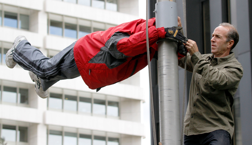 Description of . David Vissat with Brunner Advertising, works on a figure dressed as a man is suspended to appear as if it is hanging onto a flagpole in a windstorm outside an office building in Gateway Center in downtown Pittsburgh on Thursday, Sept. 15, 2011 in Pittsburgh. The display is part of a promotion by Brunner Advertising to promote an upcoming program at Pittsburgh's Carnegie Science Center called