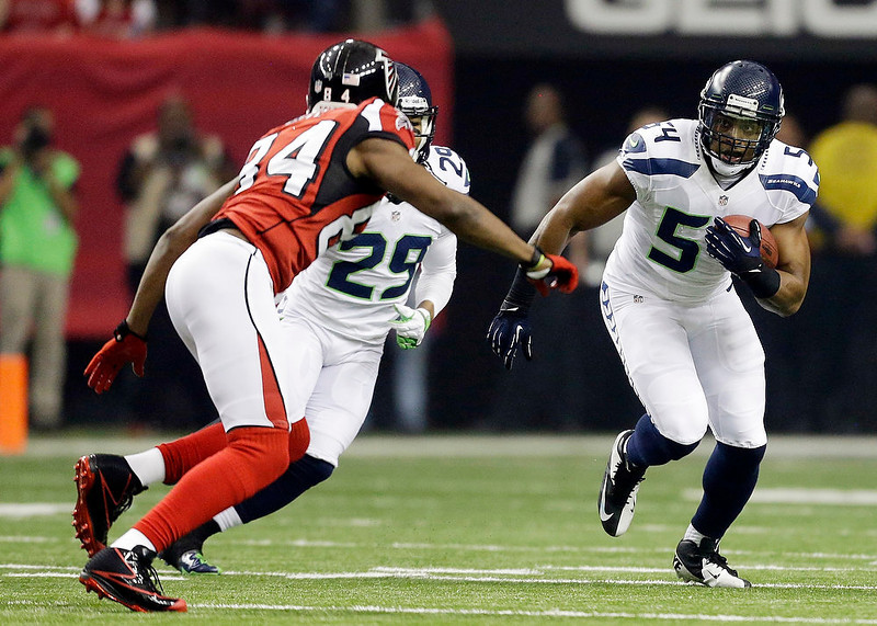 . Seattle Seahawks middle linebacker Bobby Wagner (54) runs an interception back in front of Atlanta Falcons\' Roddy White (84) during the first half of an NFC divisional playoff NFL football game Sunday, Jan. 13, 2013, in Atlanta. (AP Photo/David Goldman)