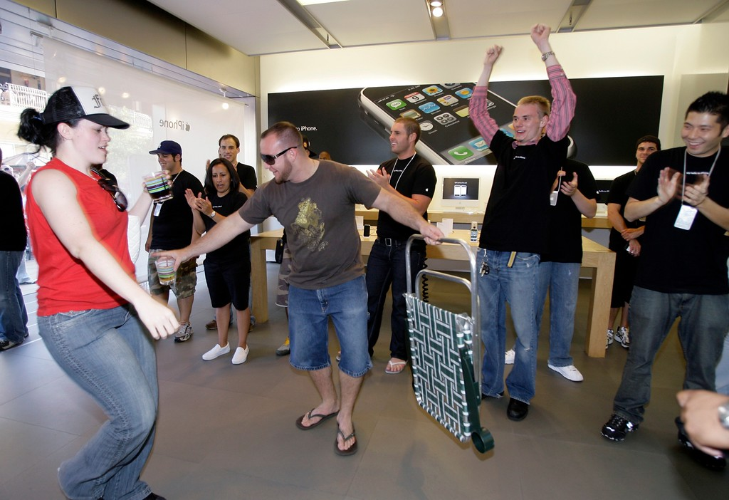 . Customers dance as they are welcomed into the Apple store to purchase the new iPhone Friday, June 29, 2007, at The Grove in Los Angeles.  (AP Photo/Damian Dovarganes)