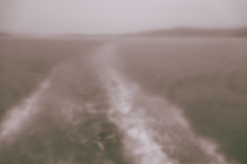Blurry and foggy stern side view of the outside from aboard the ferry.
