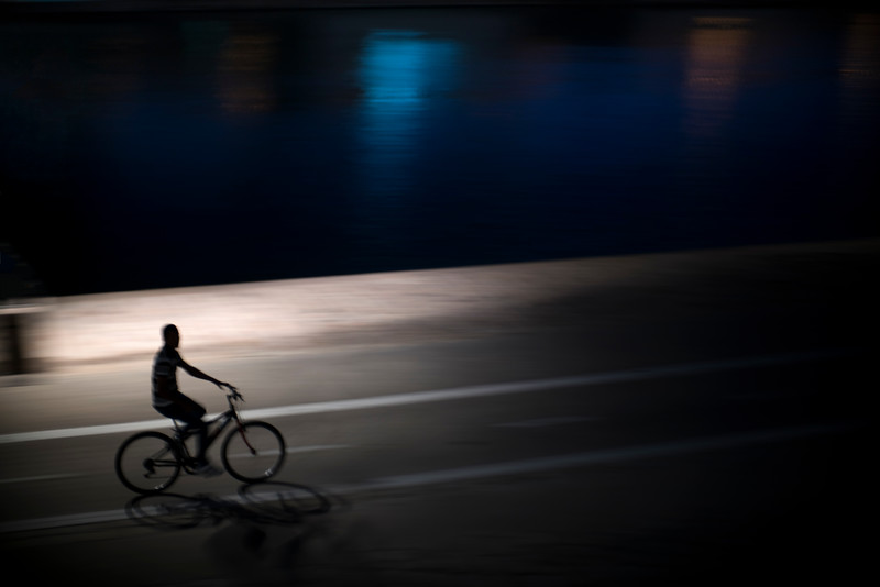 Cyclist riding by the Guadalquivir river at night, Seville, Spain