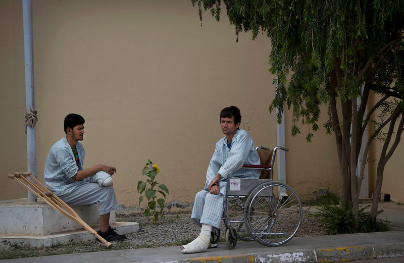 . Two injured Afghan Army soldiers relax outside the ANA military hospital at the Kandahar Air Base in Kandahar, Afghanistan on Sunday, April 21, 2013. The Afghan NGO Safety Office issued a report in April 2013 saying that the current re-escalation trend in Afghanistan will be preserved throughout the entire season and that 2013 is set to become the second most violent year after 2011, which suffered 2,755 such attacks in the first three months of the year. (AP Photo/Anja Niedringhaus)