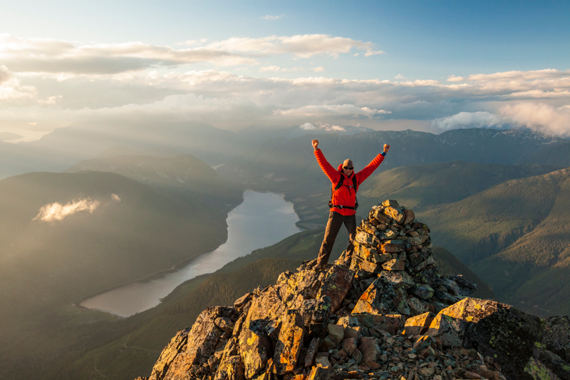 A climber celebrates after reaching the summit of a rocky mountain.