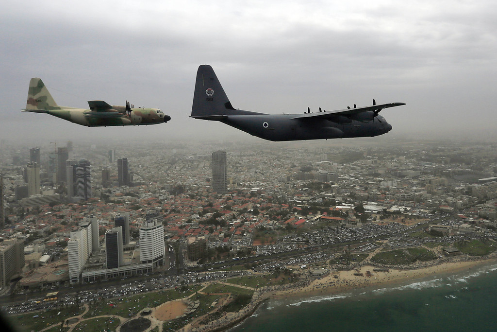 . Israeli Air Force military cargo airplane C-130J Super Hercules, right, and Hercules C-130, left, fly over the city of Tel Aviv during an air show celebrating Independence Day Tuesday, May 6, 2014. Israel is celebrating its annual Independence Day, marking 66 years since the founding of the state in 1948. (AP Photo/Tsafrir Abayov)