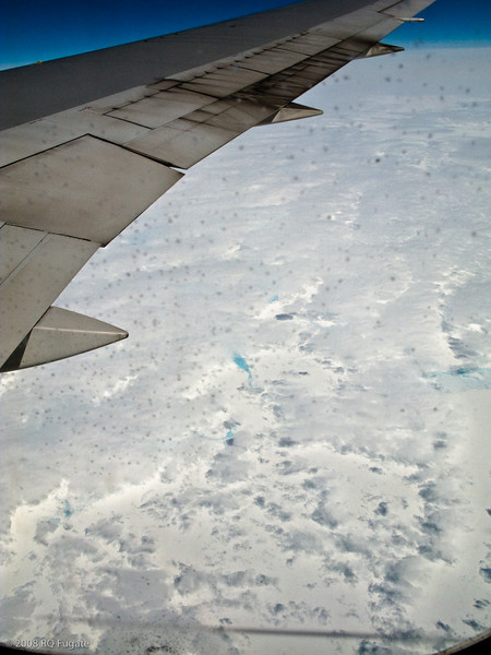 The spots are ice crystals on the outside of the airplane's window.