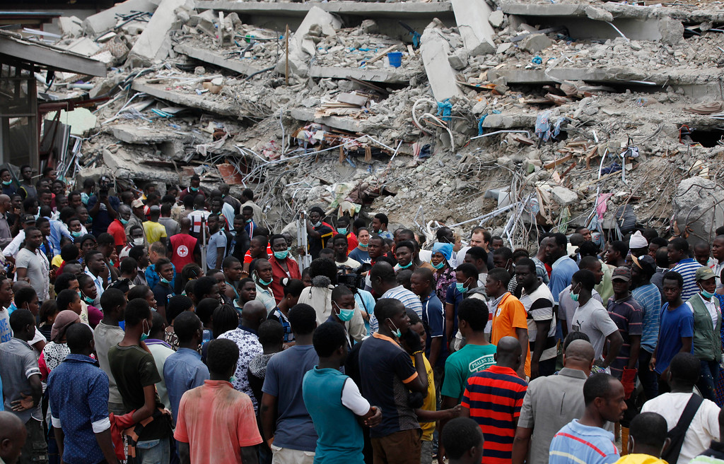 . Rescue workers gather at the sits of a collapsed building belonging to the Synagogue Church of All Nations in Lagos, Nigeria, Saturday, Sept, 13. 2014. The building was being extended, adding 2 additional floors when it collapsed. (AP Photo/Sunday Alamba)