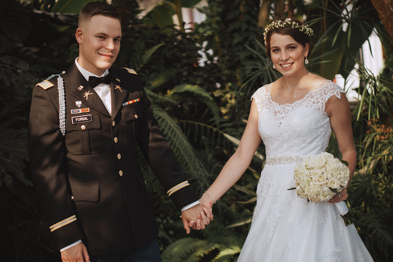 Inside a lush, tropical, greenhouse, the bride and groom smile and hold hands.