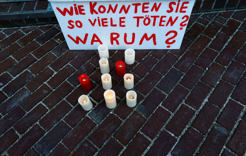 ". A placard and candles are seen early morning in front of a courthouse, where the trial against Beate Zschaepe, a member of the neo-Nazi group National Socialist Underground (NSU), began in Munich on May 6, 2013. The surviving member of NSU blamed for a series of racist murders that scandalized Germany and shamed its authorities goes on trial on Monday in one of the most anticipated court cases in recent German history. The trial in Munich will focus on 38-year-old Zschaepe, who is charged with complicity in the murder of eight Turks, a Greek and a policewoman between 2000-2007, as well as two bombings in immigrant areas of Cologne, and 15 bank robberies. Four others charged with assisting the NSU will sit with Zschaepe on the bench. The placard reads, ""How could they kill so many\"". REUTERS/Kai Pfaffenbach"
