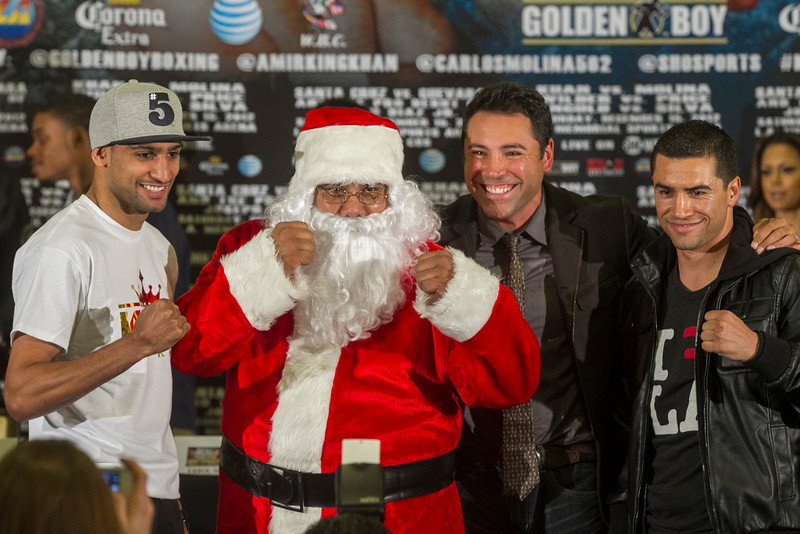 . Golden Boy Promotions president Oscar De La Hoya second from right, and someone dressed as Santa Claus present Amir ìKingî Khan, left, and Carlos Molina, right, during a boxing news conference in Los Angeles Wednesday, Dec. 12, 2012. Khan and Molina are scheduled to fight in a junior welterweight bout on Saturday at the Los Angeles Sports Arena. (AP Photo/Damian Dovarganes)
