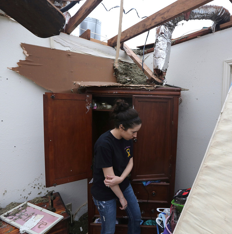 . Lauren Seay looks for items to recover in the bedroom of home that was destroyed by a tornado in Cleburne, Texas, Thursday, May 16, 2013. (AP Photo/LM Otero)