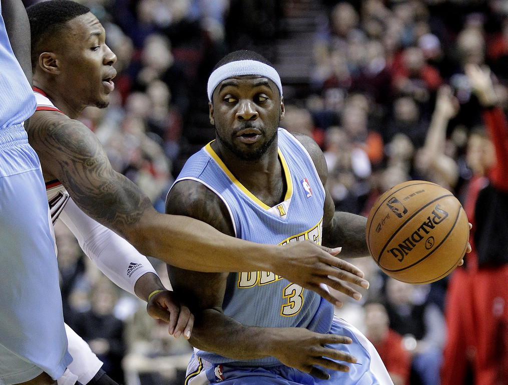 . Denver Nuggets guard Ty Lawson, right, drives on Portland Trail Blazers guard Damian Lillard during the first half of an NBA basketball game in Portland, Ore., Thursday, Jan. 23, 2014. (AP Photo/Don Ryan)