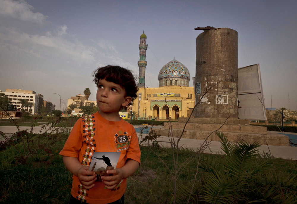 . Hussein, 3, poses in Firdous Square in Baghdad with a photograph of the same site showing the statue of Saddam Hussein being pulled down by U.S. forces and Iraqis by Associated Press photographer Jerome Delay on April 9, 2003. Ten years ago on live television, U.S. Marines memorably hauled down a Soviet-style statue of Saddam, symbolically ending his rule. Today, that pedestal in central Baghdad stands empty. Bent iron beams sprout from the top, and posters of anti-American Shiite cleric Muqtada al-Sadr in military fatigues are pasted on the sides. Photo taken on March 14, 2013. (AP Photo/Maya Alleruzzo)