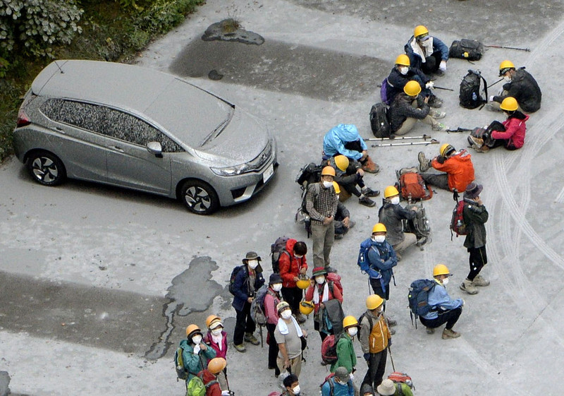. Climbers descended to a parking lot located halfway up Mt. Ontake rest after fleeing from the volcano eruption, in Kiso in Nagano Prefecture, central Japan, Saturday, Sept. 27, 2014. With a sound likened to thunder, the 3,067-meter (10,062-foot) mountain spewed large white plumes high into the sky, sending people fleeing, covering surrounding areas in ash and trapping more than 250 climbers. (AP Photo/Kyodo News)