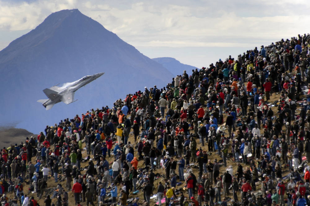 Description of . A crowd watches an F/A-18 Hornet fighter aircraft of the Swiss Air Force on October 11, 2012  doing a flight demonstration of the Swiss Air Force over Axalp in the Bernese Oberland.  AFP PHOTO / FABRICE  COFFRINI/AFP/Getty Images