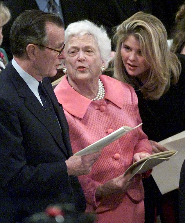 . From left, former President George Bush, wife Barbara Bush and granddaughter Jenna Bush share a moment while singing during the National Prayer Service in celebration of the 54th Presidential Inaugural at the National Cathedral Sunday, Jan. 21, 2001, in Washington. (AP Photo/Rick Bowmer)