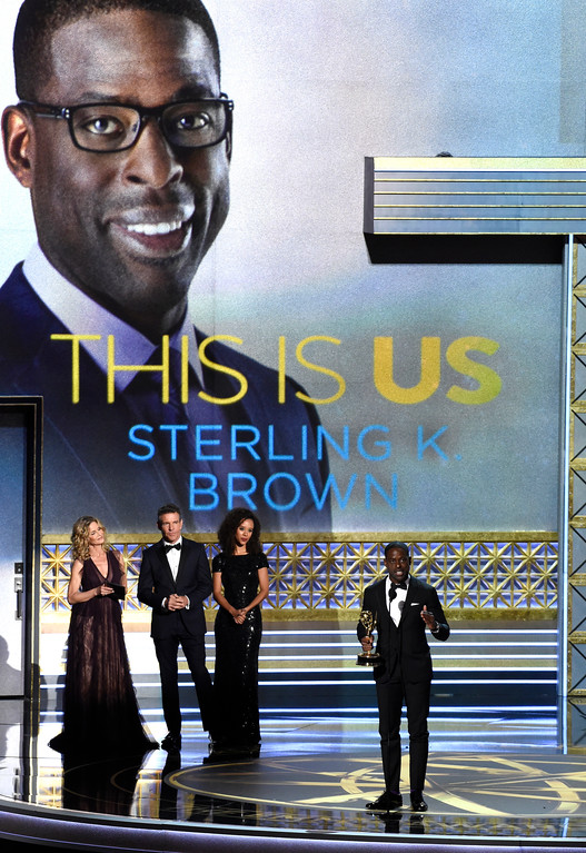 ". Sterling K. Brown, center, accepts the award for outstanding lead actor in a drama series for ""This Is Us\"" as Kyra Sedgwick, left, and Dennis Quaid, center right, look on at the 69th Primetime Emmy Awards on Sunday, Sept. 17, 2017, at the Microsoft Theater in Los Angeles. (Photo by Chris Pizzello/Invision/AP)"