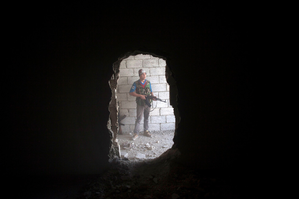 . FILE - A Free Syrian Army fighter takes cover in a building during clashes against the Syrian Army in Aleppo, Syria, Tuesday, Sept. 25, 2012. (AP Photo/Manu Brabo, File)