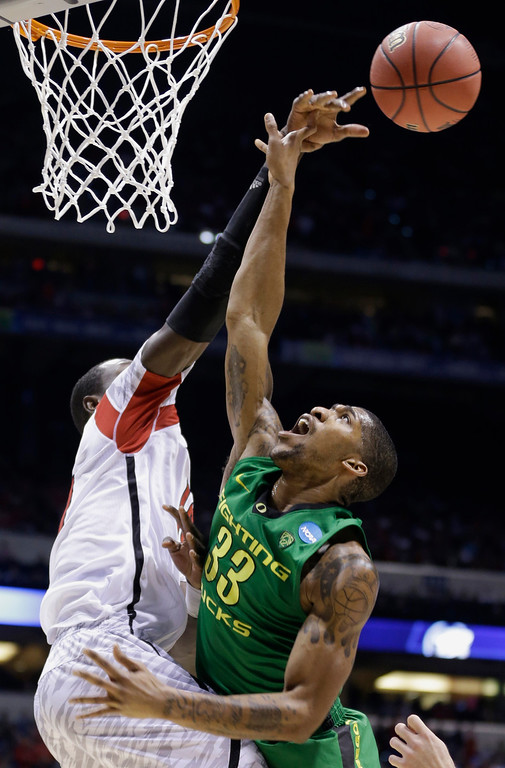 . Louisville center Gorgui Dieng blocks a shot by Oregon forward Carlos Emory (33) during the second half of a regional semifinal in the NCAA college basketball tournament, Friday, March 29, 2013, in Indianapolis. Louisville won 77-69. (AP Photo/Michael Conroy)