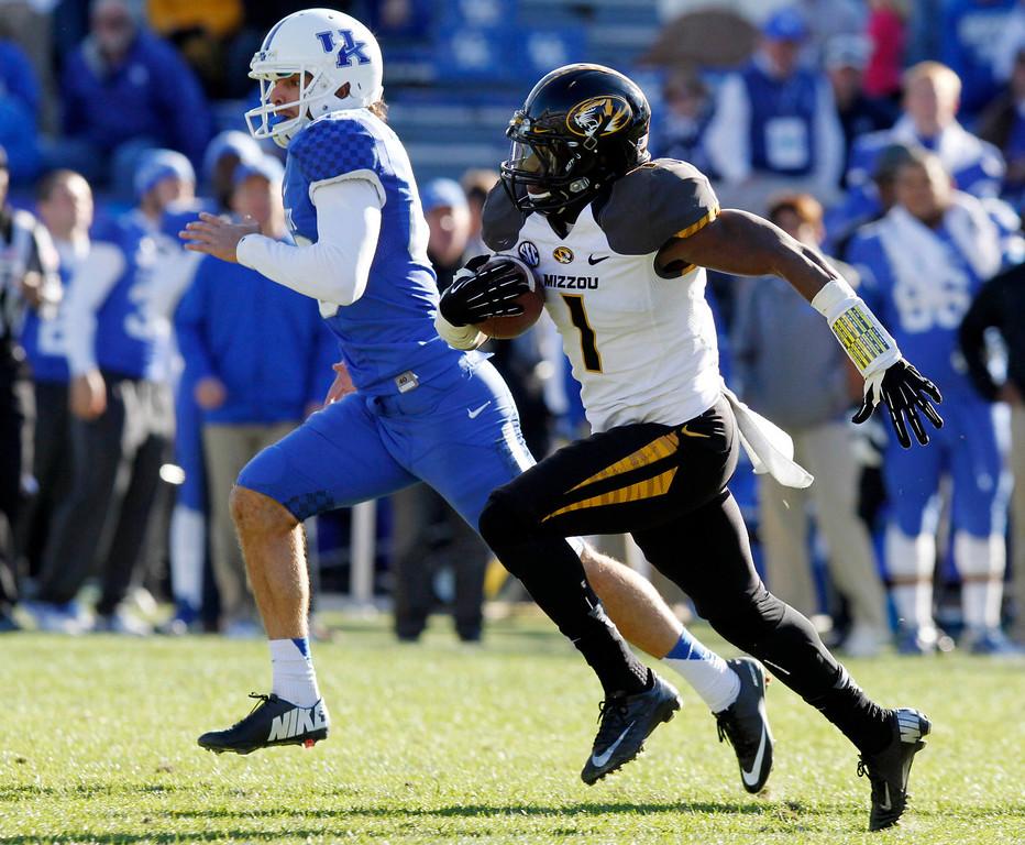 . Missouri\'s John Gibson (1) runs past Kentucky kicker Joe Mansour, left, during the third quarter of an NCAA college football game, Saturday, Nov. 9, 2013, in Lexington, Ky. Missouri won 48-17. (AP Photo/James Crisp)