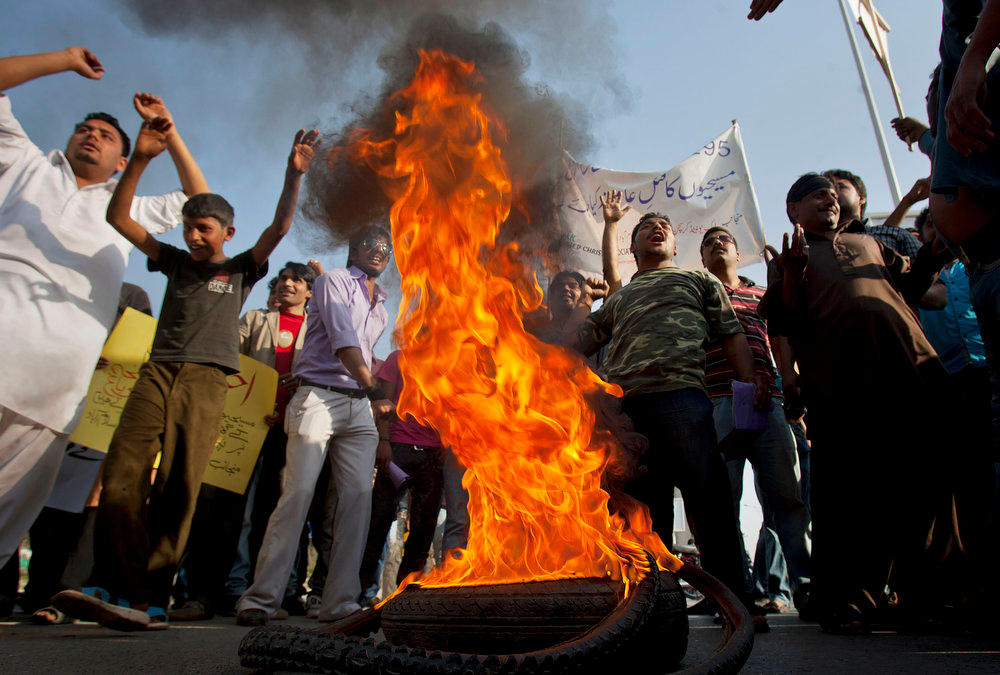 . Pakistani Christians chant slogans after they burn a tire during a demonstration demanding that the government rebuild their homes after they were burned down following an alleged blasphemy incident, in Islamabad, Pakistan, Sunday, March 10, 2013. The incident in Lahore began on Friday, March 8, 2013 after a Muslim accused a Christian man of blasphemy, an offense that in Pakistan is punished by life in prison or death. (AP Photo/Anjum Naveed)