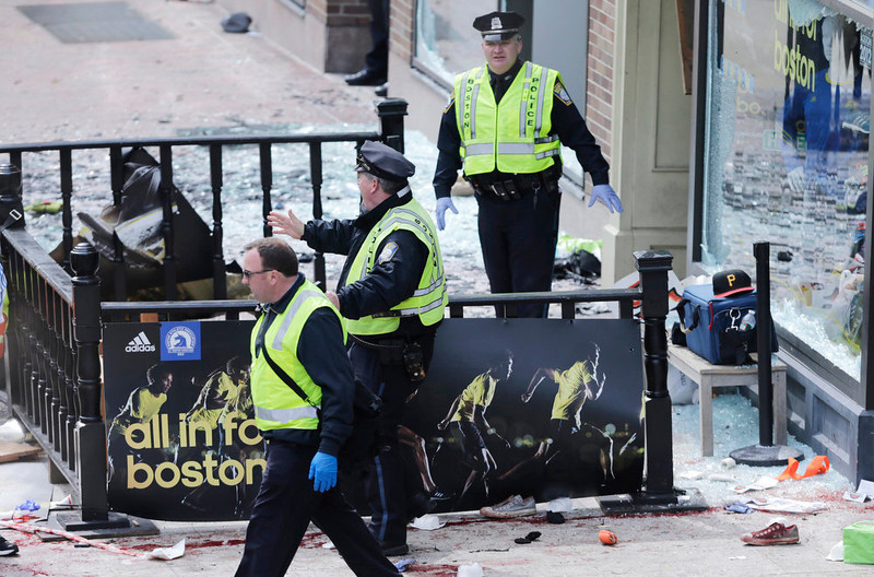 . Boston police clear an area following an explosion near the finish line of the 2013 Boston Marathon in Boston, Monday, April 15, 2013. Two explosions shattered the euphoria of the Boston Marathon finish line on Monday, sending authorities out on the course to carry off the injured while the stragglers were rerouted away from the smoking site of the blasts. (AP Photo/Charles Krupa)