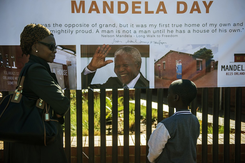 . A South African woman and her son stand in front of the Soweto Mandela House yard as various activities marking International Mandela Day take place in front of the house turned museum of the late global Icon Nelson Mandela on July 18, 2014 in Johannesburg. Mandela Day is a global call to action that celebrates the idea that each individual has the power to transform the world, the ability to make an impact. Nelson Mandela International Day (or Mandela Day) is an annual international day in honour of Nelson Mandela, celebrated each 18 July (on Mandela\'s birthday). The day was officially declared by the United Nations in November 2009, with the first UN Mandela Day held on 18 July 2010.         (GIANLUIGI GUERCIA/AFP/Getty Images)