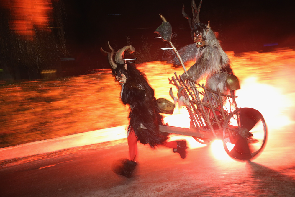 . A member of the Haiminger Krampusgruppe dressed as the Krampus creature pulls another on a fiery cart to the town square during the annual Krampus night in Tyrol on December 1, 2013 in Haiming, Austria. Krampus, in Tyrol also called Tuifl, is a demon-like creature represented by a fearsome, hand-carved wooden mask with animal horns, a suit made from sheep or goat skin and large cow bells attached to the waist that the wearer rings by running or shaking his hips up and down. Krampus has been a part of Central European, alpine folklore going back at least a millennium, and since the 17th-century Krampus traditionally accompanies St. Nicholas and angels on the evening of December 5 to visit households to reward children that have been good while reprimanding those who have not. However, in the last few decades Tyrol in particular has seen the founding of numerous village Krampus associations with up to 100 members each and who parade without St. Nicholas at Krampus events throughout November and early December.  (Photo by Sean Gallup/Getty Images)