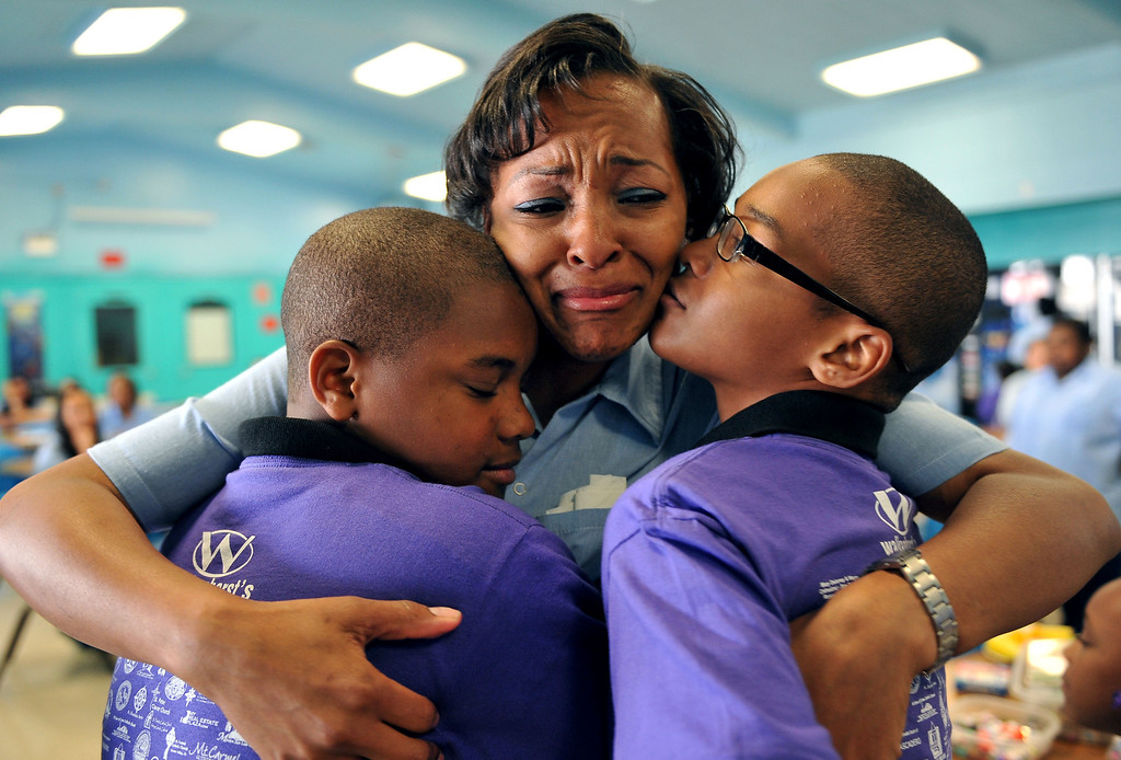 . 5/4/13 - Sequarier McCoy hugs her sons, Tarrell Smith, 11, left and LaVertis Smith, 12, right during a visit at the California Institution for Women. The mothers and children were united by the non-profit organization entitled Get On The Bus which provides an annual event of free transportation for the children and their caregivers to the prison. The visit becomes more of an event, with snacks, lunch, arts, crafts, photos, keepsakes and plenty of hugs and kisses. The program began in 2000 with one bus one prison and 17 kids. Today children are able to visit their mothers and fathers with 60 buses, seven prisons and more than a thousand kids. Photo by Brittany Murray / Staff Photographer