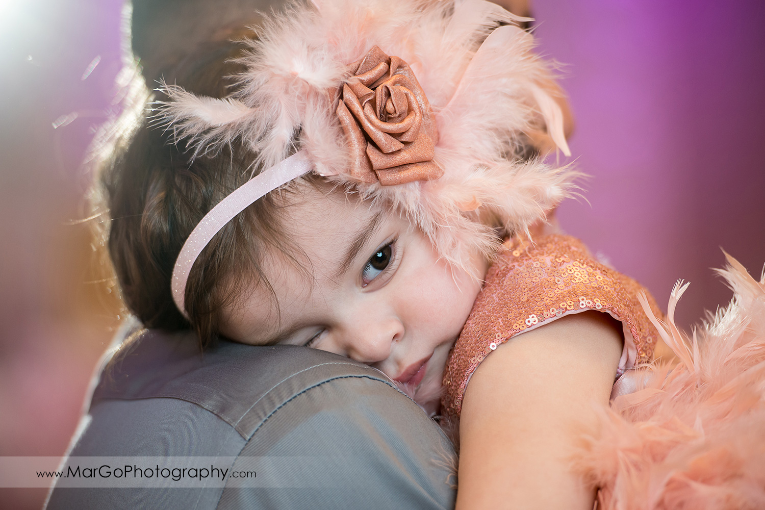 birthday girl with flower and feather hair band resting on dad's arm at Newark Oasis Palace