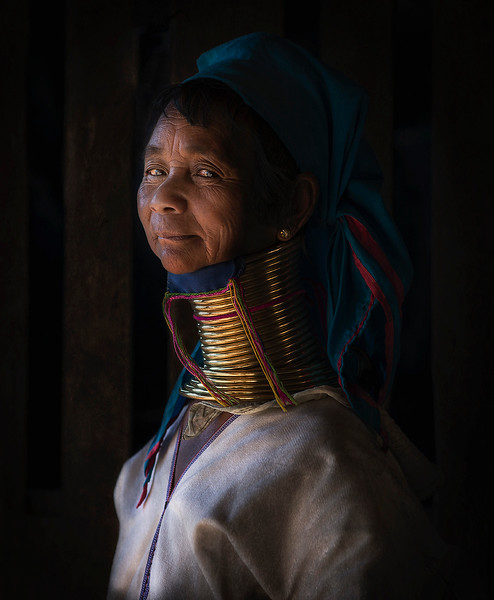 Women of the Kayan tribes identify themselves by their forms of dress. Women of the Kayan Lahwi tribe are well known for wearing neck rings, brass coils that are placed around the neck, appearing to lengthen it.  Girls first start to wear rings when they are around 5 years old. Over the years, the coil is replaced by a longer one and more turns are added. The weight of the brass pushes the collar bone down and compresses the rib cage. The neck itself is not lengthened; the appearance of a stretched neck is created by the deformation of the clavicle. Many ideas regarding why the coils are worn have been suggested, often formed by visiting anthropologists, who have hypothesized that the rings protected women from becoming slaves by making them less attractive to other tribes. It has also been theorised that the coils originate from the desire to look more attractive by exaggerating sexual dimorphism, as women have more slender necks than men. It has also been suggested that the coils give the women resemblance to a dragon, an important figure in Kayan folklore. The coils might be meant to protect from tiger bites, perhaps literally, but probably symbolically.  Kayan women, when asked, acknowledge these ideas, and often say that their purpose for wearing the rings is cultural identity (one associated with beauty).  The coil, once on, is seldom removed, as the coiling and uncoiling is a lengthy procedure. It is usually only removed to be replaced by a new or longer coil. The muscles covered by the coil become weakened. Many women have removed the rings for medical examinations. Most women prefer to wear the rings once their clavicle has been lowered, as the area of the neck and collarbone often becomes bruised and discolored. Additionally, the collar feels like an integral part of the body after ten or more years of continuous wear.  Kayah State, Myanmar 2017