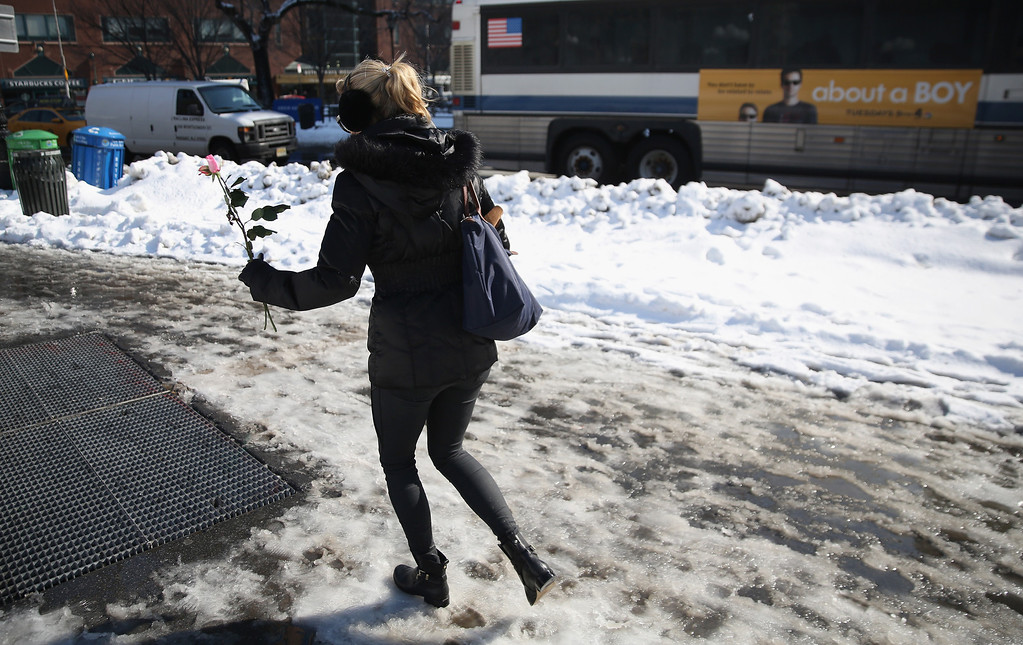 . A woman carries roses through the slush of Union Square on Valentine\'s Day, February 14, 2014 in New York City. New Yorkers dug out from a foot of snow, much of which by afternoon had melted to slush on city streets and sidewalks. (Photo by John Moore/Getty Images)