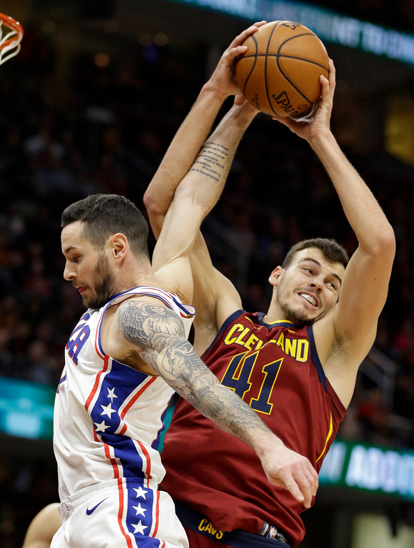 . Philadelphia 76ers\' JJ Redick, left, fouls Cleveland Cavaliers\' Ante Zizic (41) during the first half of an NBA basketball game, Saturday, Dec. 9, 2017, in Cleveland. (AP Photo/Tony Dejak)