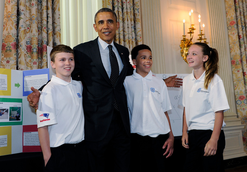 . President Barack Obama stands with, from left, Gerry McManus, 13,  Daisjaughn Bass, 13, and Brooke Bohn, 14, all of Hudson, Mass., as he tours the 2014 White House Science Fair exhibits that are on display in the State Dining Room at the White House in Washington, Tuesday, May 27, 2014. The students showed Obama their basketball catapult.  (AP Photo/Susan Walsh)