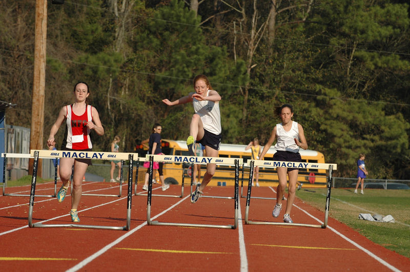 """On the back straight, we've now got Girls' 300m hurdle action underway. L-r, Darcy Watson, Hannah Ciupalo, and Alexandra Pijut attack the second of eight sets of 30"""" hurdles, 35m apart."""