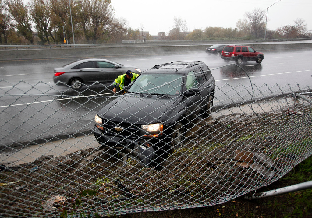 . A Freeway Service Patrol worker helps a motorist right their vehicle after it spun out in the rain on Highway 87 in San Jose, Calif., Thursday morning, Dec. 11, 2014. (Karl Mondon/Bay Area News Group)